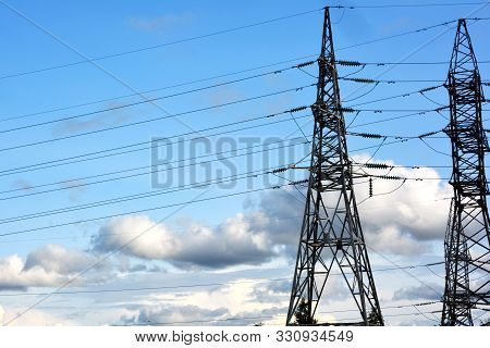 Towers of electric main with the wires against the blue sky with clouds. High voltage lines and power pylons.Transformer with high-voltage wires technogenic landscape, high-voltage power lines. poster