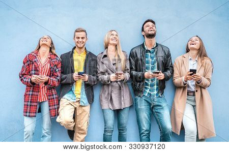 Happy Friends Group Using Smartphones Against Blue Wall At University College Break - Young People H