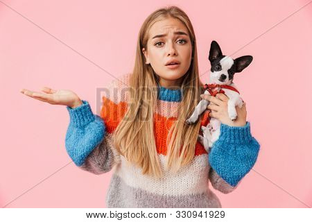 Cute lovely confused girl playing with her pet chihuahua isolated over pink background, shrugging shoulders