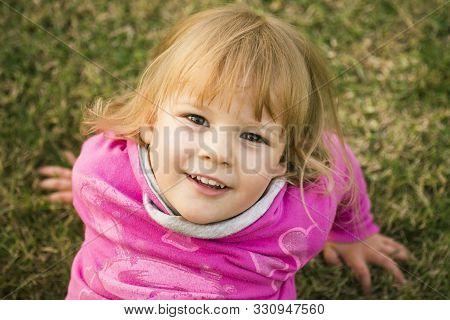 Child Portrait Of Blond Hair Cute Little Girl Outdoors On Grass.