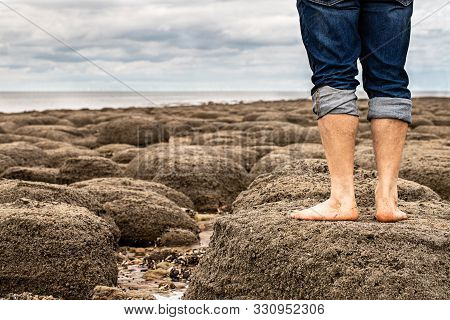 Man Standing  Barefoot On The Beach Of Stones On The Seashore