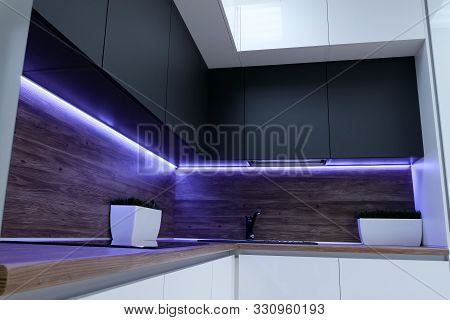 black ergonomic cupboards decorated with amazing violet neon strip light above wooden kitchen set surface poster