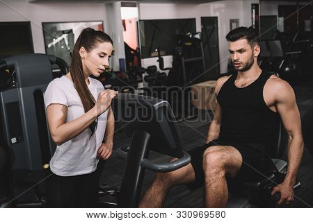 Attractive Trainer Instructing Handsome Sportsman Working Out On Recumbent Elliptical Trainer