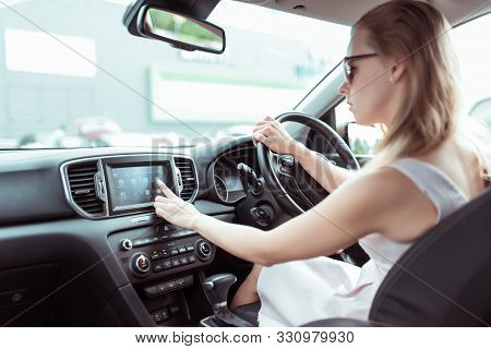 Woman Driving Car, Presses Finger On Touch Screen, Selects Application On Internet, Activates Radio