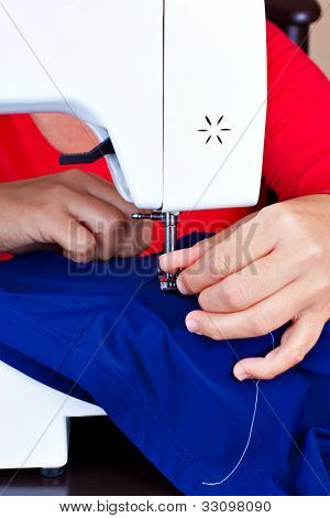 Close-up of hands working on a sewing machine