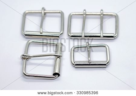 Metal Buckles For Dog Collars With A Rounded Tongue. Silver Buckles Of Different Sizes On A White Ba