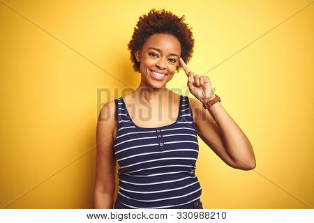 Beauitul african american woman wearing summer t-shirt over isolated yellow background Smiling pointing to head with one finger, great idea or thought, good memory