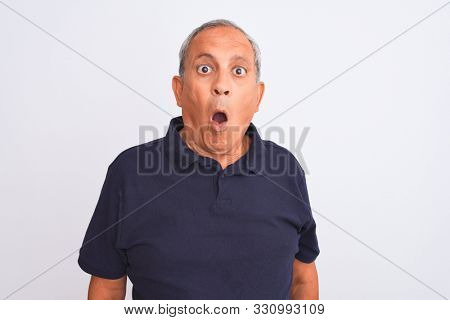 Senior grey-haired man wearing black casual polo standing over isolated white background afraid and shocked with surprise expression, fear and excited face.