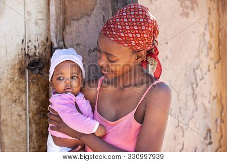 Single young African mother in a village in Botswana, the drama of single mothers from the third world
