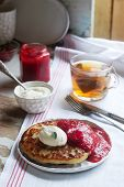Curd pancakes with strawberry sauce, sour cream and raspberries, and herbal tea on a light table. Rustic style. poster