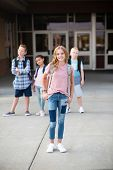 Group of Elementary school students standing in front of their school. Smiling and hanging out together after school. Selective focus on the cute girl in front poster
