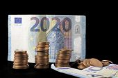 New fiscal year 2020 represented with euro bills and coin stacks isolated on black. Conceptual image of the economical situation and possible upcoming crisis. poster