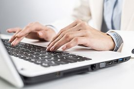 Man In Business Suit Sitting At Desk And Working At Laptop Computer. Close-up Of Male Hands Typing O