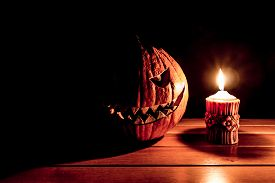 Carved Spooky Halloween Pumpkin At Hot Burning Candle Fire Flame. Big Helloween Autumn Symbol With M