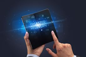 Businessman holding a foldable smartphone with DISASTER RECOVERY inscription, cyber security concept