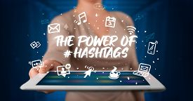Young business person working on tablet and shows the inscription: THE POWER OF HASHTAGS
