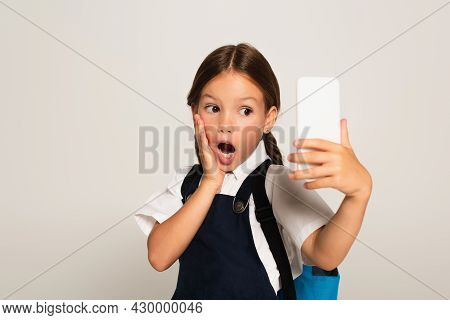 Astonished Schoolkid Touching Face While Taking Selfie On Cellphone Isolated On Grey