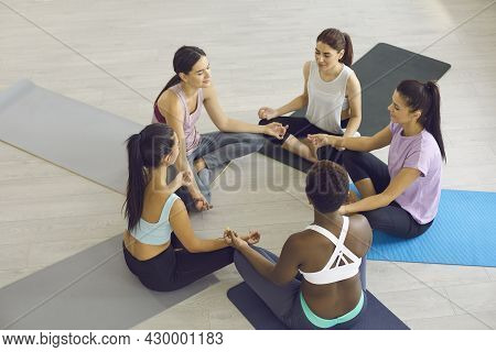 Diverse Group Of Happy Women Sitting On Gym Floor During Yoga Class And Meditating