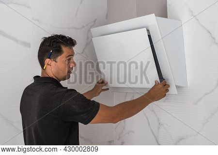 Man Assembling An Extractor Fan In A Kitchen