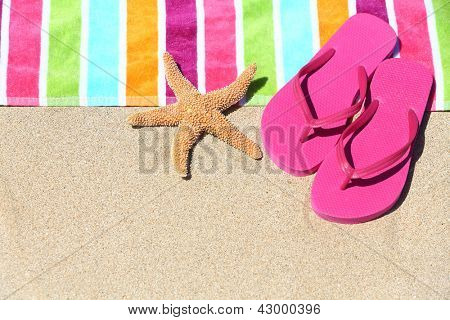 poster of Tropical beach vacation holiday and travel concept with a colourful striped beach towel and vibrant pink sandal flip flip thongs on pristine sand with a starfish at an idyllic coastal beach resort.