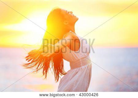 Gozo - mulher feliz livre apreciando o pôr do sol. Mulher bonita de vestido branco, abraçando a su dourado