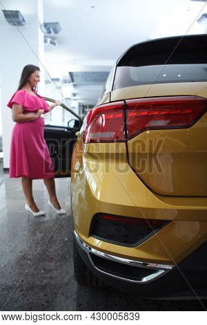 Selective Focus On A Car Female Customer Choosing Auto To Buy At Dealership On Background