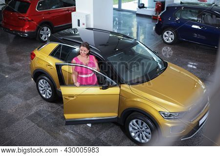 Top View Shot Of A Cheerful Female Buying New Car At The Dealership