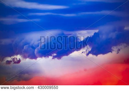 Dark Blue Rain Clouds Against Background Of Bright Scarlet Red Sunset Sky. Natural Sky Background Wi
