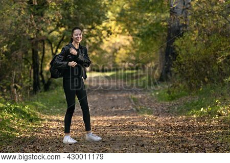 Girl Walks Along The Alley Of The Autumn Park. Happy Girl In Black Clothes In The Forest. Alley, Pro