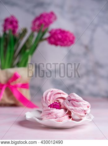Sweet Pink Marshmallows On A Plate With A Vase Of Spring Flowers On The Table Against The Background