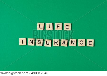 Words Life Insurance By Wooden Blocks On Green Background. Insurance Concepts.