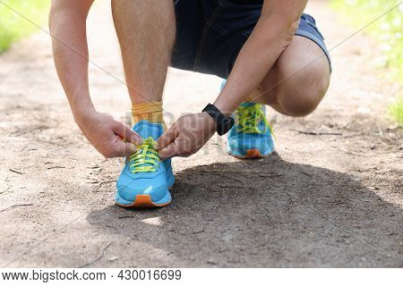 Man Shoelaces Laces On Sports Fashion Sneakers In Park