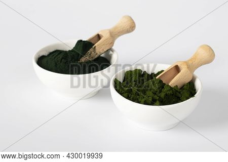 Organic Algae Chlorella And Spirulina In Powder Form In White Bowls With Wooden Scoops On White Back