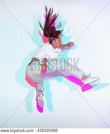 Jumping Mixed Race Young Girl Jumping In Colourful Neon Studio Light. Female Dancer Performer Moving
