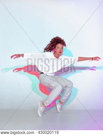 Dancing Mixed Race Young Girl In Colourful Light. Female Dance Standing On Tiptoe. Contemporary Hip