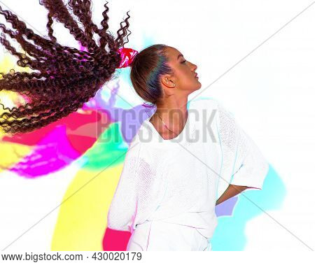 Dancing Mixed Race Young Girl In Colourful Rainbow Light. Contemporary Female Hip Hop Dancer With Af