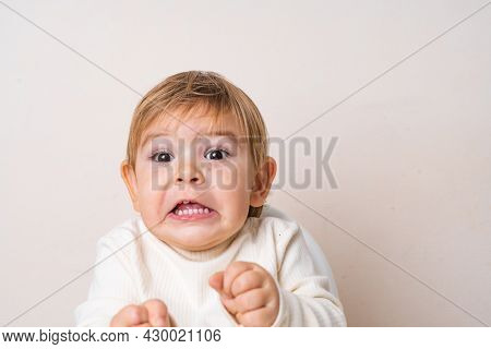 Toddler Baby Sitting On The High Chair And Doing Funny Grimace. Teeth Of The Baby. Face Expression
