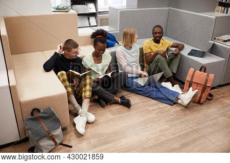 High Angle View At Diverse Group Of Young Students Studying Together While Sitting On Floor In Colle