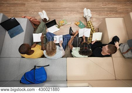 Top Down View At Diverse Group Of Young Students Studying Together While Sitting On Floor In College