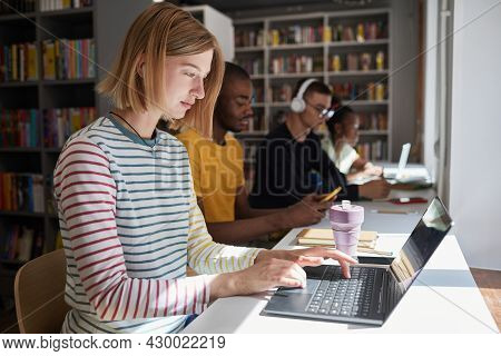 Side View Portrait Of Young Woman Studying With Group Of Students In School Library, Copy Space