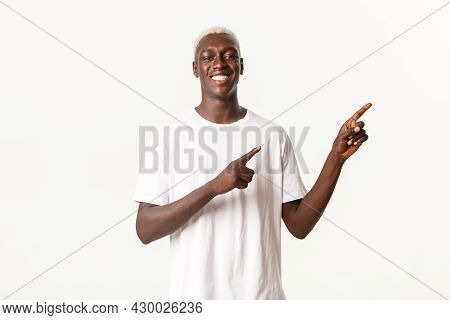 Portrait Of Satisfied Happy African-american Blond Man, Smiling Pleased And Pointing Fingers Upper R