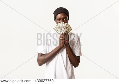 Portrait Of Greedy, Cunning African-american Young Man Looking Pleased With Smug Face While Holding