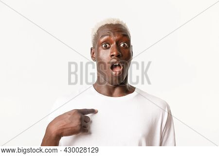 Portrait Of Startled, African-american Blond Guy Looking Surprised As Pointing At Himself With Dropp