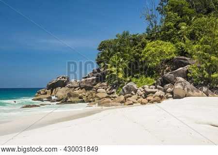 Beautifully shaped granite boulders and a perfect white sand at the famous Anse Georgette, Praslin island, Seychelles