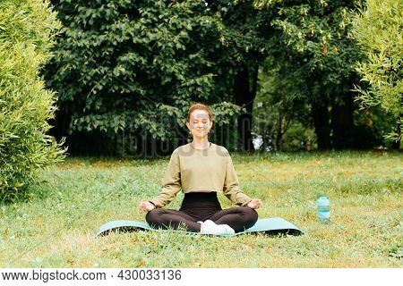 Meditation, Mindfulness And Spirituality Concept. Young Woman In Sportswear Meditating In Lotus Posi