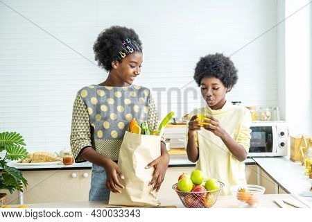 Two Adorable African American Children, Brothers And Sisters, Have Just Returned From The Market. An