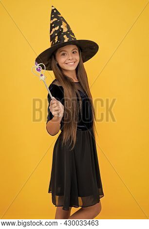 Happy Kid Wear Witch Hat Holding Magic Wand To Create Enchantment On Halloween, Halloween Magic