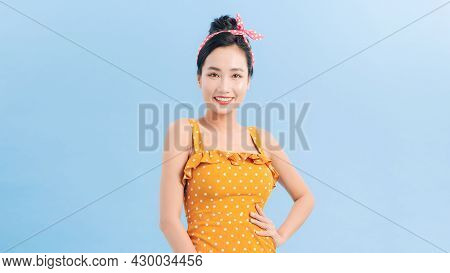 Young Beautiful Female In Polka-dot Dress Smiling And Posing
