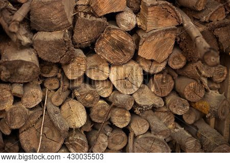 Wall Old Firewood, Background Of Dry Chopped Firewood Logs In A Pile. Preparation For The Winter.