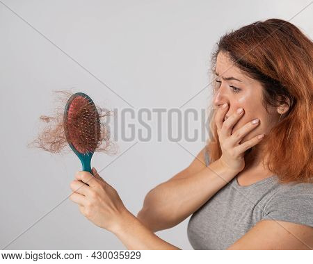 Caucasian Woman With A Grimace Of Horror Holds A Massage Comb With A Bun Of Hair. Hair Loss And Fema